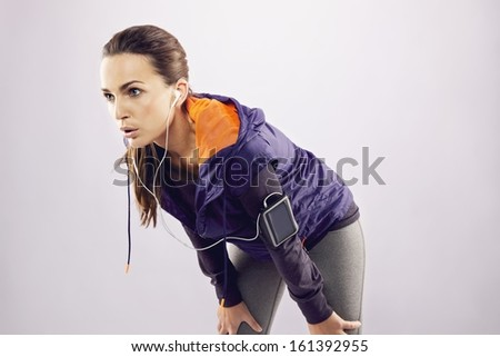 Tired caucasian female athlete leaning over after jogging. Young woman in sportswear relaxing after a jog on grey background - stock photo