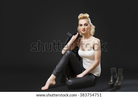 Tired caucasian girl wearing tight leather pants and white top and high heels next to her sitting down - stock photo