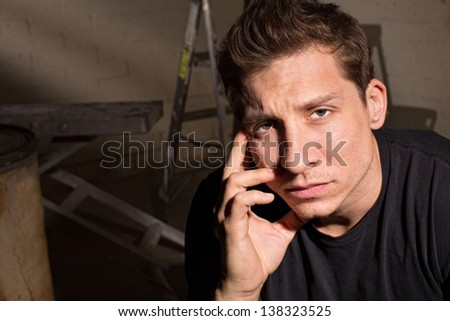 Tired Caucasian guy indoors with hand near face - stock photo