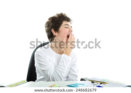Tired Caucasian smooth-skinned boy sits in front of homework wearing a white long sleeve t-shirt and yawns covering his mouth with right hand
