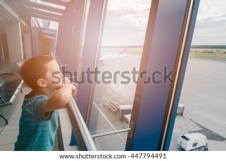 Tired child at the airport, traveling and waiting near window for his plane. Canceled flight