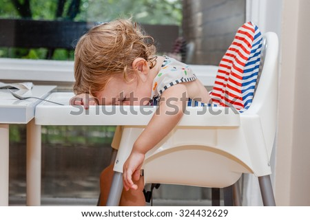 Tired child sleeping in highchair after the lunch. Baby over eating and fall asleep just after feeding, lying his face on the table tray. - stock photo