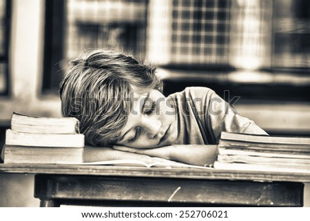 Tired child sleeping while studying in the primary school classroom. - stock photo