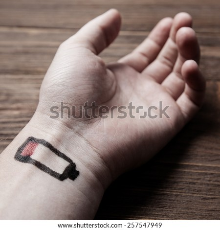 Tired concept with battery low on hand - stock photo
