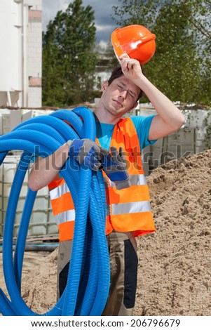 Tired construction worker holding pipes on his shoulder - stock photo
