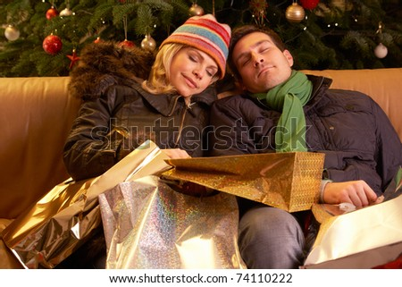 Tired Couple Returning After Christmas Shopping Trip - stock photo
