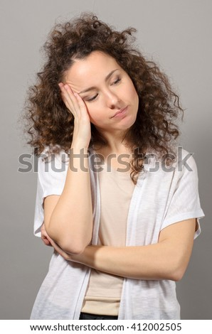 Tired curly woman after work on grey background