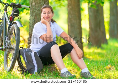 tired cyclist resting in a park near a tree - stock photo