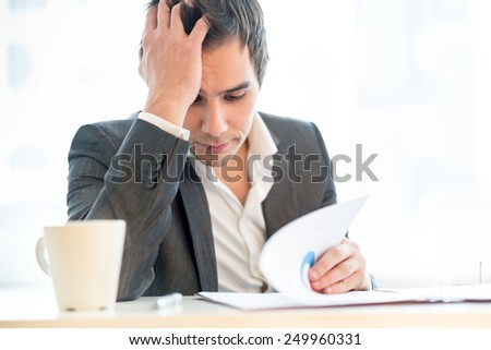 Tired diligent hardworking businessman resting his head on his hand as he reads through a lengthy report with a mug of energizing coffee alongside him, close up view of him sitting at his desk - stock photo