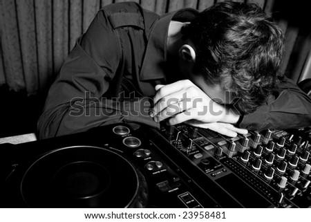 Tired DJ sleeping in a nightclub - stock photo