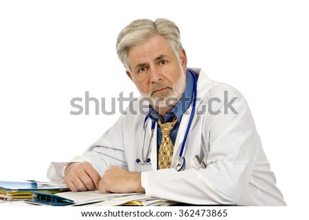 Tired doctor at his desk/ Experienced Doctor Sitting At Desk - stock photo