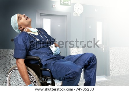 Tired doctor sleeping in a wheelchair - stock photo