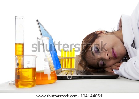 Tired doctor sleeping over laptop computer shot in laboratory - stock photo