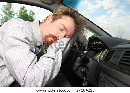 tired driver sleeps in a car - stock photo