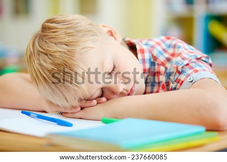 Tired elementary pupil napping by desk after lessons - stock photo