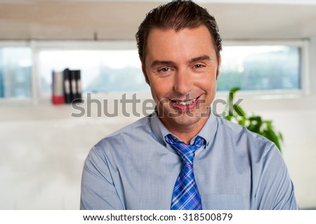 Tired executive smiling after long work day - stock photo