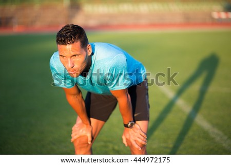 Tired exhausted young man catching breath after hard training - stock photo