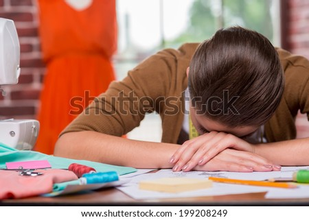Tired fashion designer. Tired young woman leaning her face at the table while sitting at her working place with mannequin standing in the background - stock photo