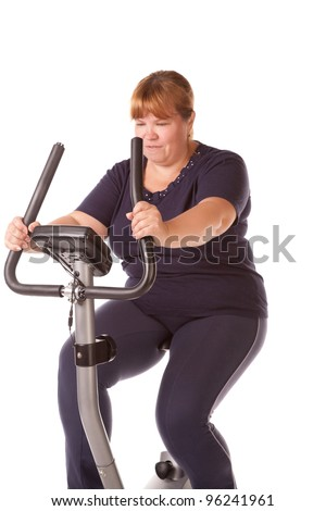 tired fat woman training on the bike - stock photo