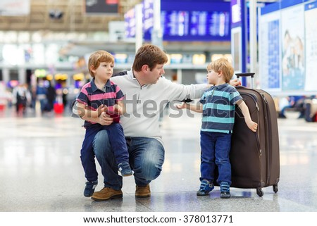 Tired father and two little sibling kids boys at the airport, traveling together. Angry family waiting. Canceled flight due to pilot strike. - stock photo