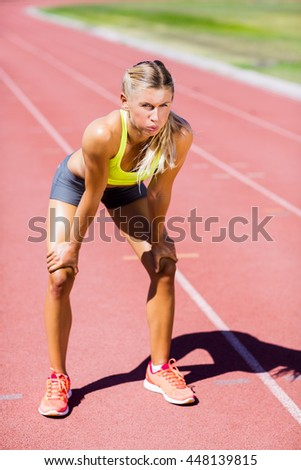 Tired female athlete standing on running track on a sunny day