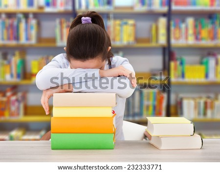 Tired female college student leaning on stack of books at desk in library