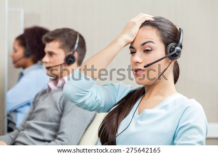Tired female customer service representative with colleagues in background at call center - stock photo