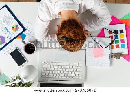 Tired female employee at workplace in office taking nap. Sleepy worker early in the morning after late night work. Creative person (designer or artist) in despair caused by deadline concept - stock photo