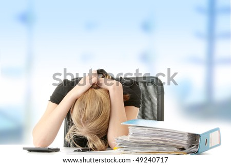 Tired female executive filling out tax forms while sitting at her desk. - stock photo