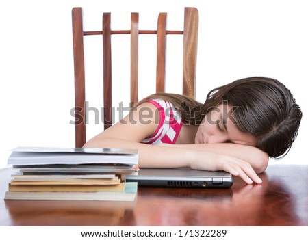 Tired female teen student sleeping over her laptop with a stack of books on the table - stock photo