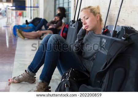 Tired female traveler waiting for departure, resting on the station floor with all her luggage. - stock photo