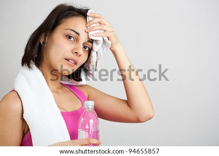 Tired fitness girl, isolated on white background - stock photo