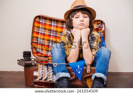 Tired from adventures. Little boy in headwear holding hands on chin and looking at camera while sitting on suitcase against brown background  - stock photo
