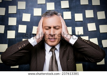 Tired from it all. Frustrated senior man in formalwear holding head in hands and keeping eyes closed while standing against blackboard with adhesive notes on it - stock photo