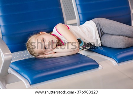 Tired gilr waiting for flight inside international airport. Flight delay concept - stock photo