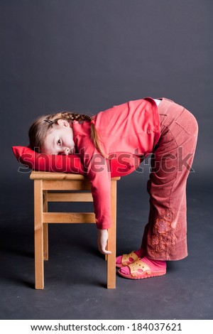 Tired girl bending on a chair with pillow, studio shot - stock photo