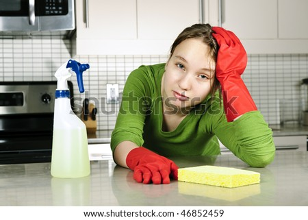 Tired girl doing kitchen cleaning chores with rubber gloves - stock photo