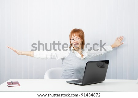 tired girl with a laptop stretches in the workplace - stock photo