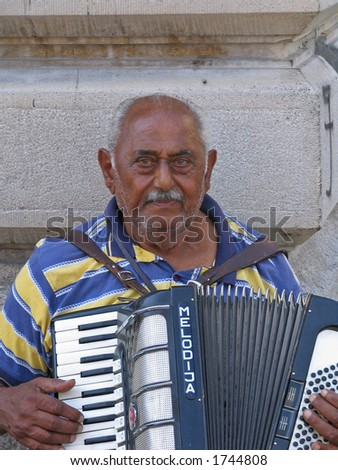 tired gypsy artist performing on the street, with sad and deep expression on his face - stock photo