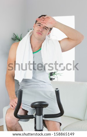 Tired handsome man exercising on exercise bike in bright living room - stock photo