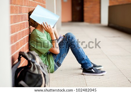 tired high school student using book cover his face - stock photo