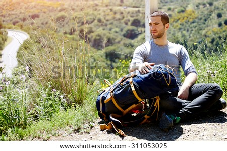 Tired hiker with backpack resting after active walk in mountains, traveler man enjoying scenery landscape view on top of hill with copy space area background for your text message or advertise content - stock photo