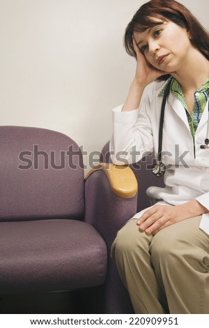 Tired Hispanic female doctor sitting with head in hand - stock photo