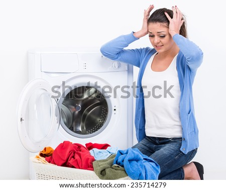 Tired housewife is doing laundry with washing machine at home. - stock photo