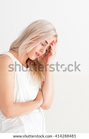 Tired ill woman with headache and flu. Unhealthy sad disappointed girl. Family conflict, illness, crisis, stress, symptom and headache concept. Ill woman on white background with free space.