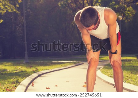 Tired jogger in the park. - stock photo