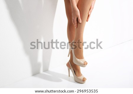 Tired legs aching, swelling. Beautiful, leggy woman in thin tights and fashionable styling - stock photo