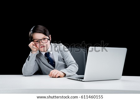 Tired little boy in formal suit and eyeglasses working with laptop isolated on black