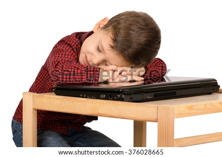 Tired little boy sleeping on the laptop computer isolated on white background