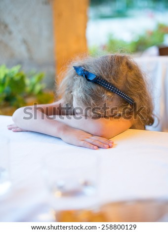 Tired little girl fell asleep at the table in restaurant. - stock photo